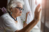 istock Senior woman looking out of window at home 1272457536