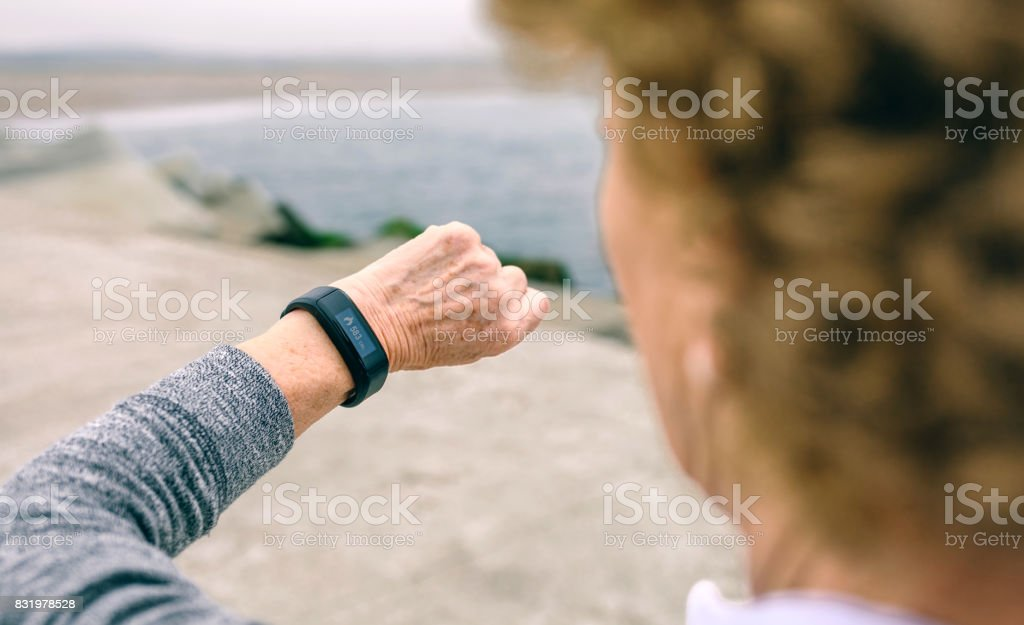 Senior woman looking smart watch stock photo