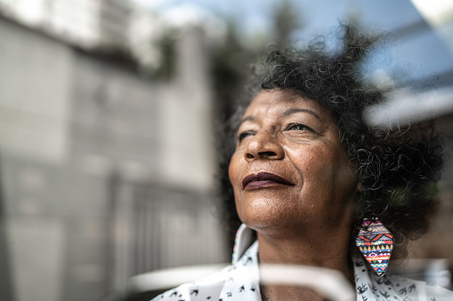 Senior woman looking through the window at home