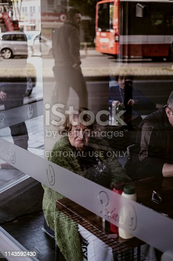 Izmir, Turkey - April 2019: Senior woman watching outside through the window of a sidewalk cafe in Alsancak district. Alsancak is a central district in Izmir city in the municipal area of Konak. Location in the center of Izmir, close to the old town, the business district and many shops, restaurants. One of the historic part of Izmir that stretches along the southern shoreline on the Gulf of Izmir.