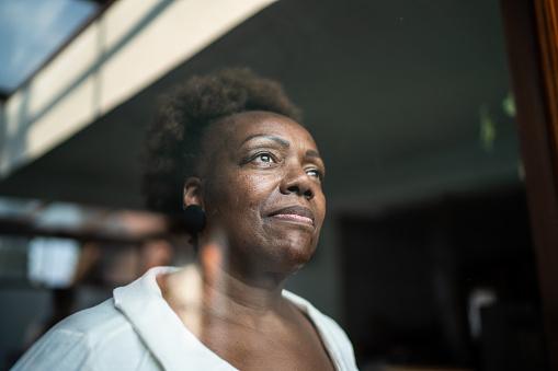 Senior woman looking through the window