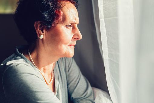 istock Senior woman looking through the window 641423136
