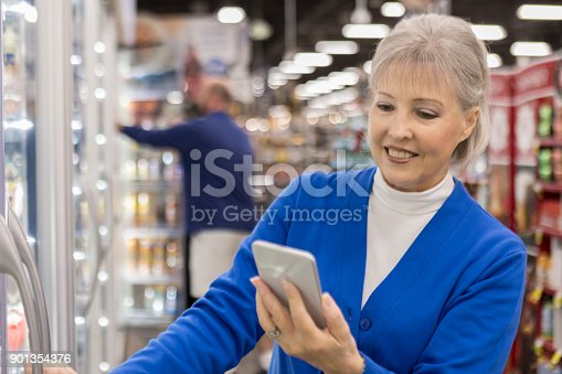 istock Senior woman looks at grocery list while shopping 901354376