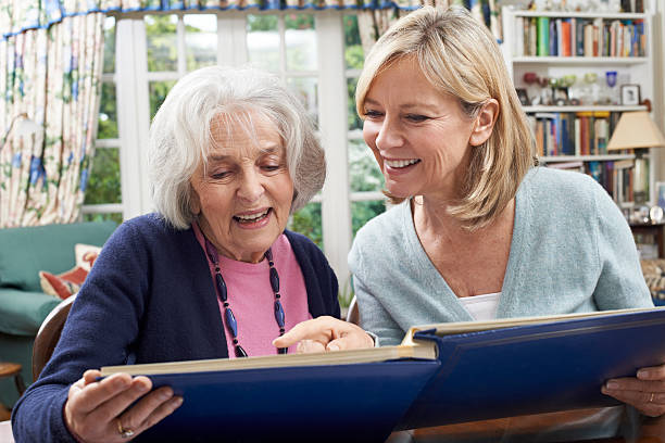 Senior Woman Looks At Photo Album With Mature Female Neighbor stock photo