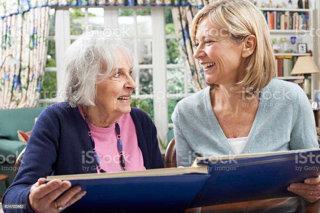 Senior Woman Looks At Photo Album With Mature Female Neighbor stock photo