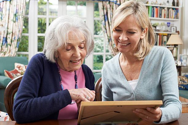 senior woman looks at photo frame with mature female neighbor - nostalji stok fotoğraflar ve resimler