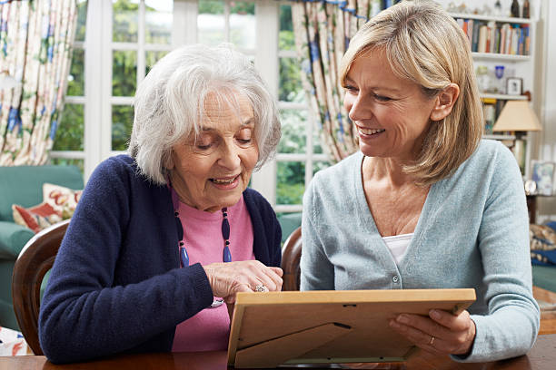 Senior Woman Looks At Photo In Frame With Mature stock photo