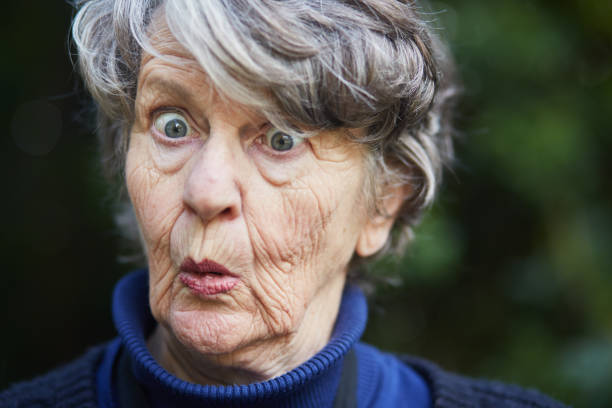 Senior woman looks shocked and fearful stock photo