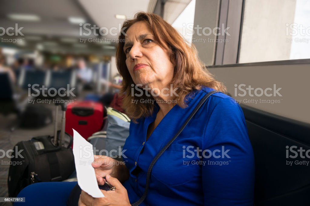 Senior Woman Looks to See Flight Boarding at Airport royalty-free stock photo