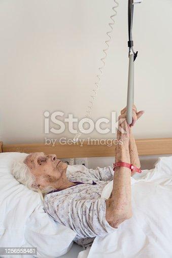istock Senior woman lying in bad in nursing home 1256558461