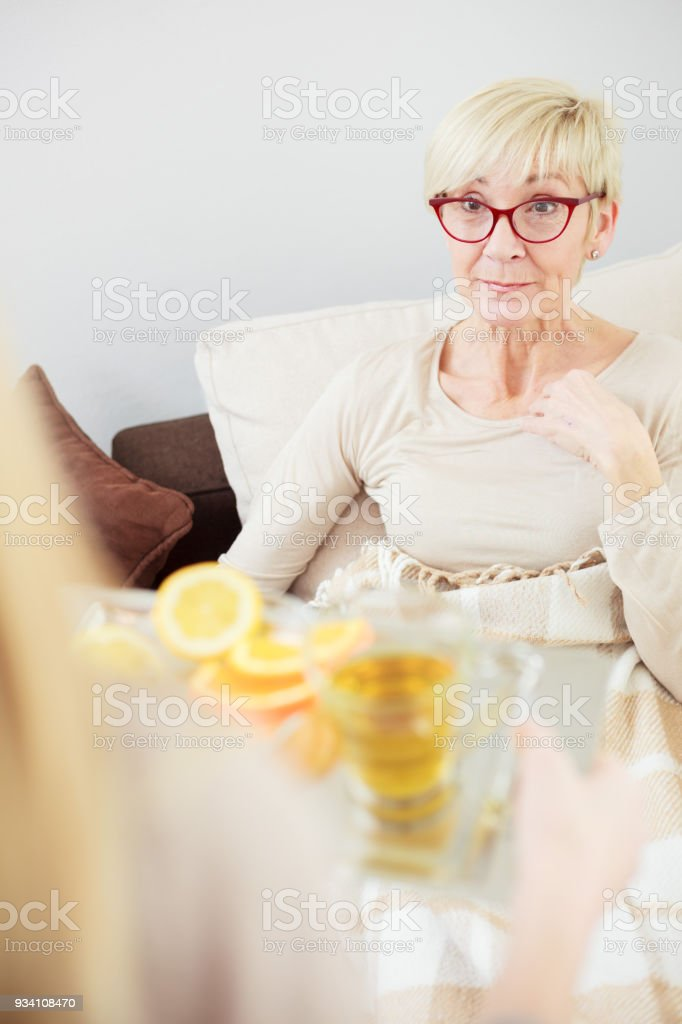 Senior woman lying in bed, daughter bringing tea and fruits. stock photo