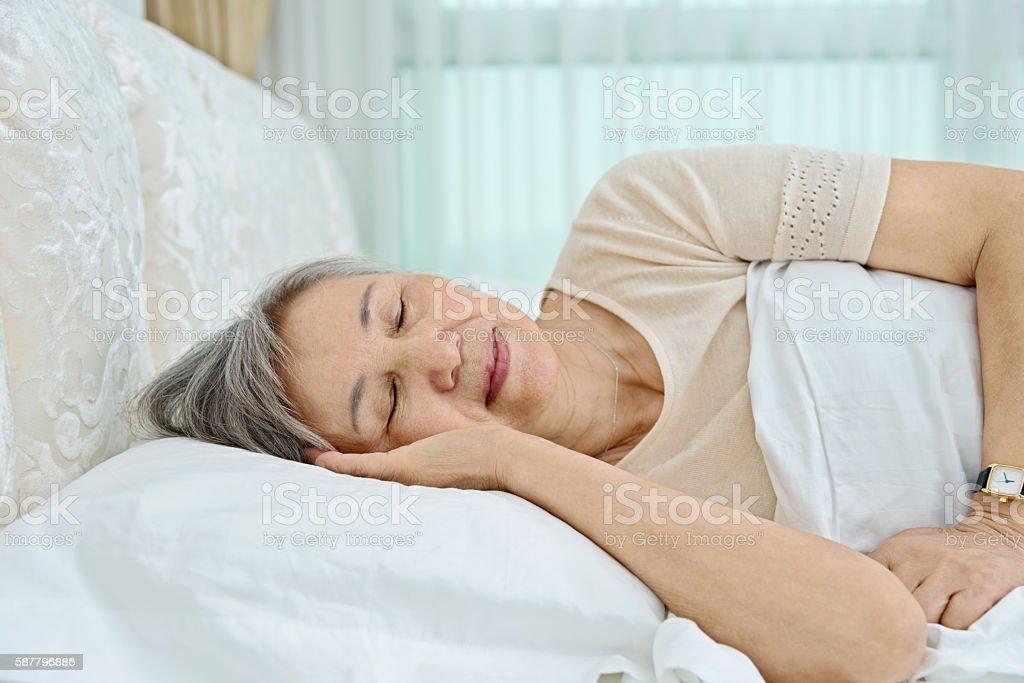 Senior woman lying in bed sleeping stock photo