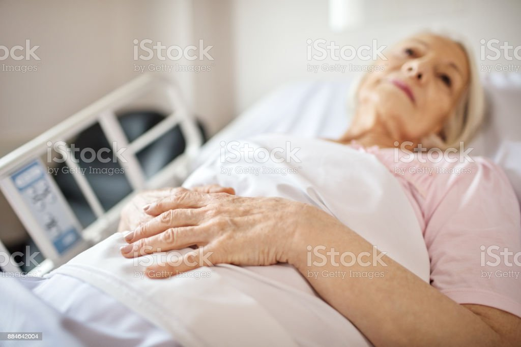 Senior woman lying on hospital bed stock photo