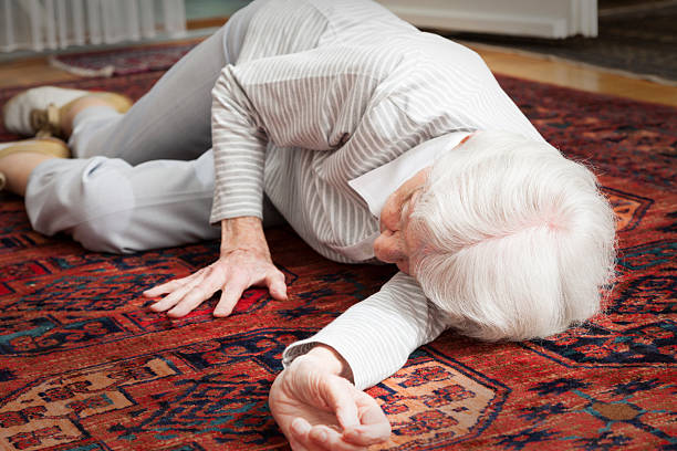senior woman lying on the floor after accident stock photo