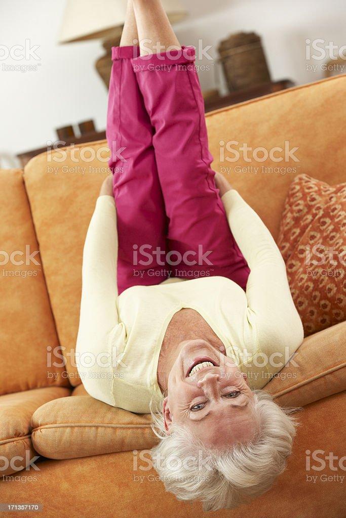 Senior Woman Lying Upside Down On Sofa At HomeSmiling