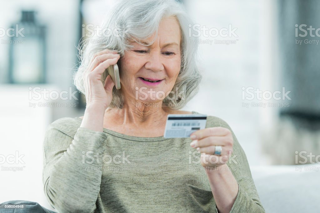 Senior Woman Making a Call With Credit Card stock photo