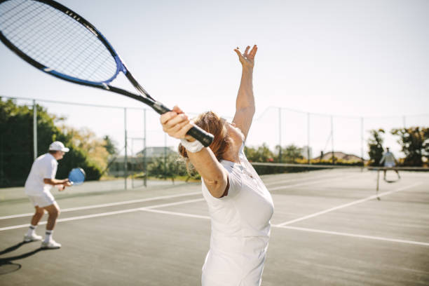 senior woman het maken van een serve tijdens het spelen van tennis - tennis stockfoto's en -beelden