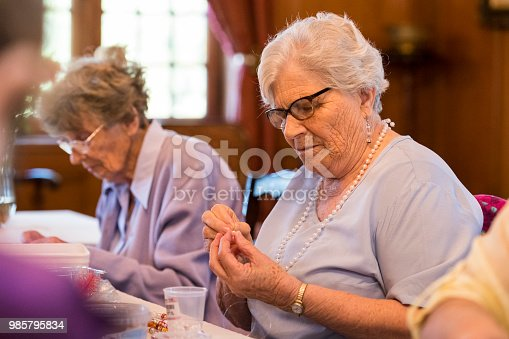 Photo of a senior woman making beaded jewelry sitting at a table