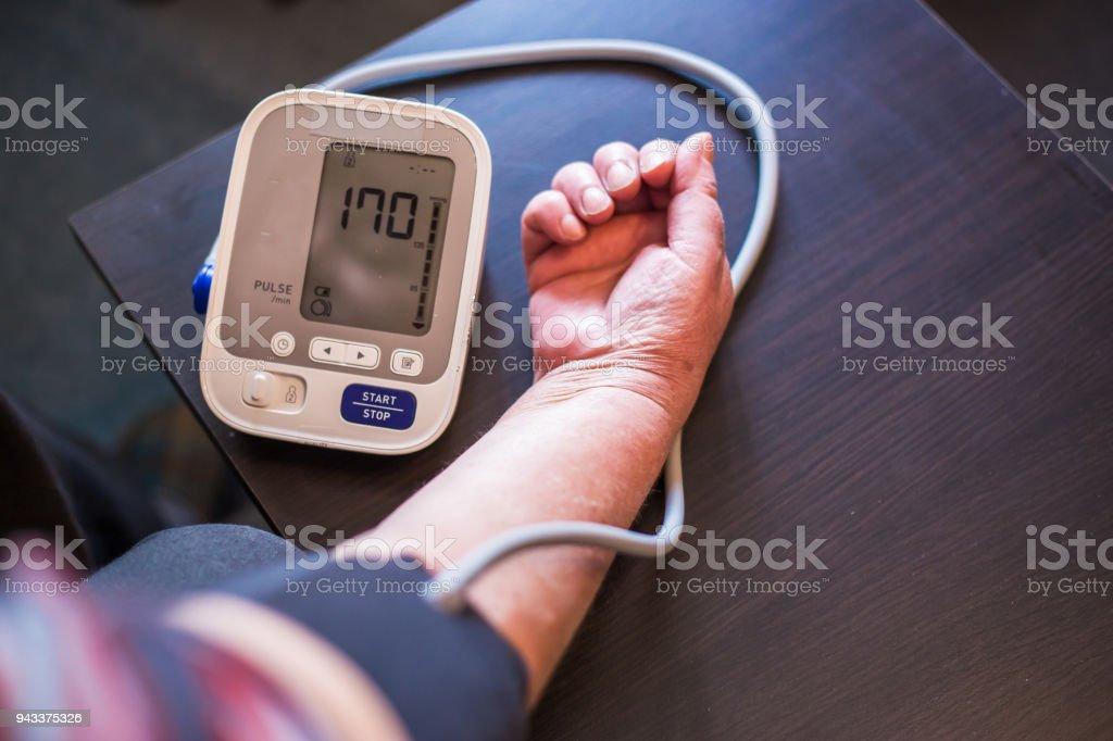 Senior woman measures pressure at home stock photo