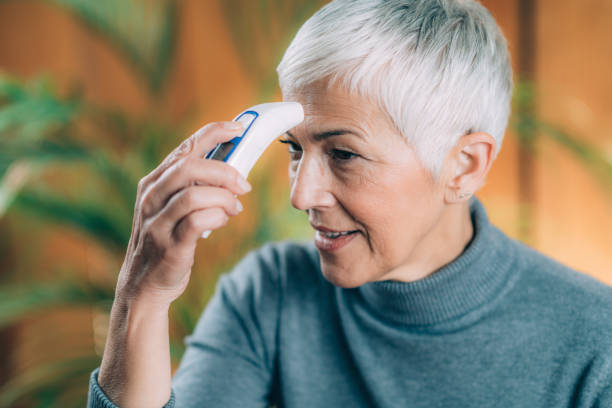 Senior Woman Messen Körpertemperatur mit kontaktlosem Digitalthermometer – Foto