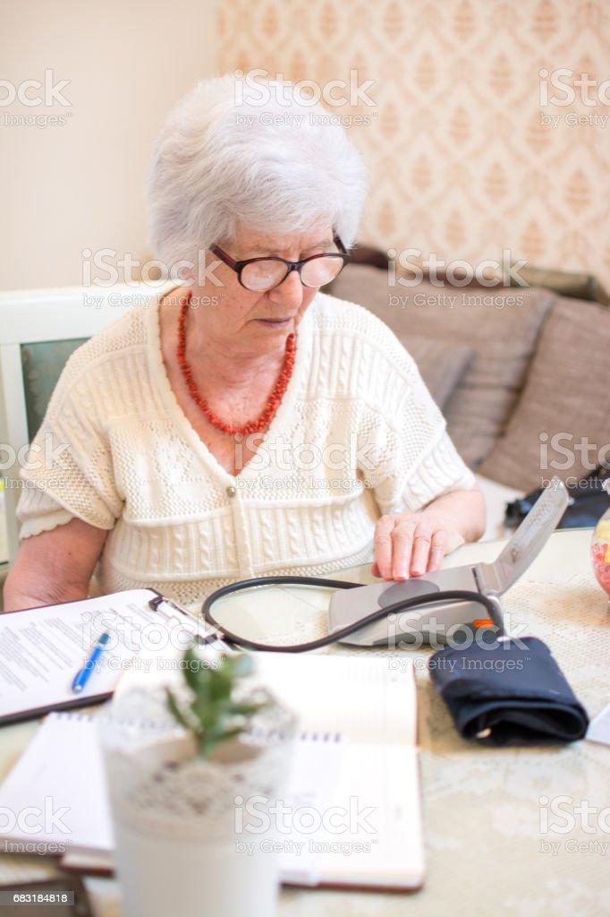 Senior woman measuring her blood pressure. Home blood pressure monitoring. 免版稅 stock photo