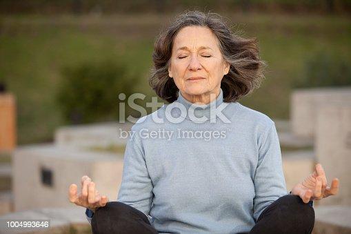 Senior woman practicing meditation in public park