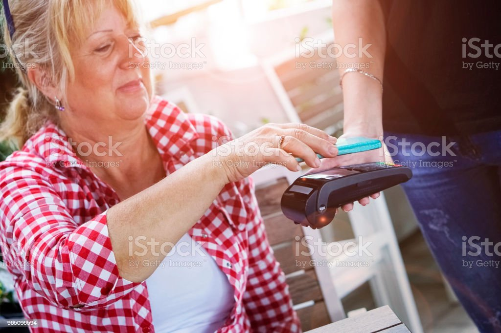 Senior woman Mobile payment in cafe royalty-free stock photo