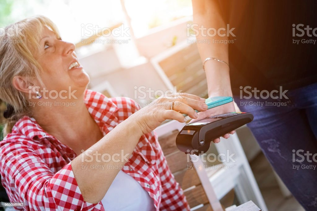 Senior woman Mobile payment in cafe zbiór zdjęć royalty-free
