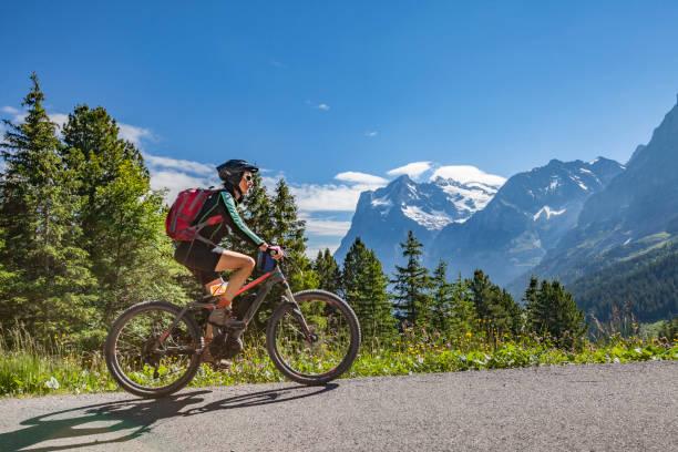 senior woman mountainbiking in grindelwald - elektrorad stock-fotos und bilder