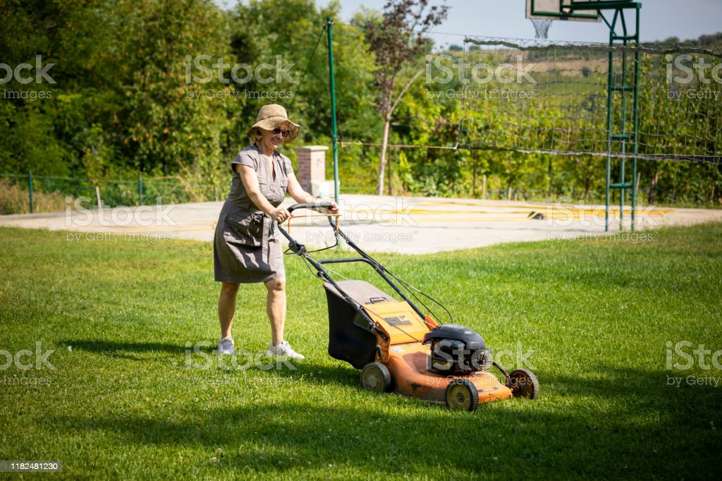 Woman mowing lawn and dancing, Stock Photo, Picture And