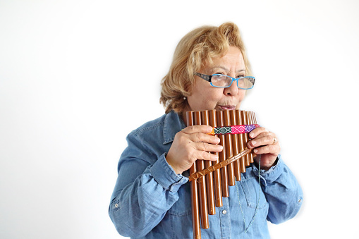 Senior woman musician playing pan flute