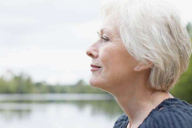 senior woman near lake - vrouw 60 stockfoto's en -beelden