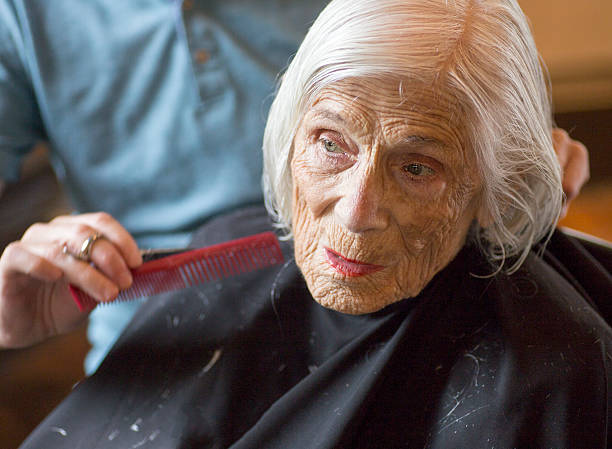 Senior woman observing, at the hairdresser stock photo