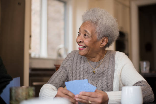 Senior woman of African descent playing cards stock photo