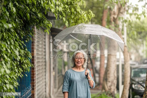 A happy senior woman on the street of Taipei is looking into the camera.