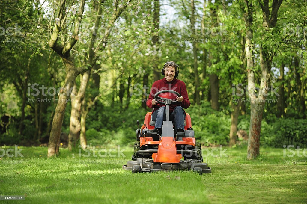 Senior woman on a lawn mower stock photo