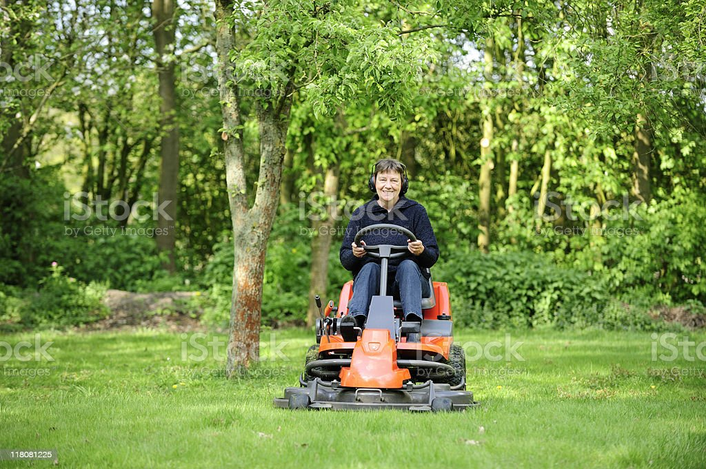 Woman mowing lawn with electric lawn mower Stock Photo