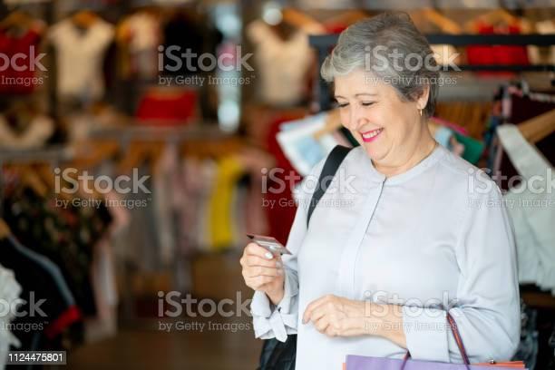 Mujer Senior En Un Pie De Juerga Compras En Una Tienda De Ropa Mirando Sonriente De Tarjeta De Crédito Foto De Stock Y Más Banco De Imágenes De A La Moda