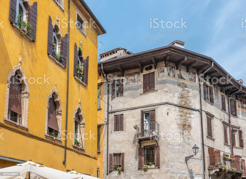 Senior woman on a slanted balcony in the old town of Verona, Italy stock photo