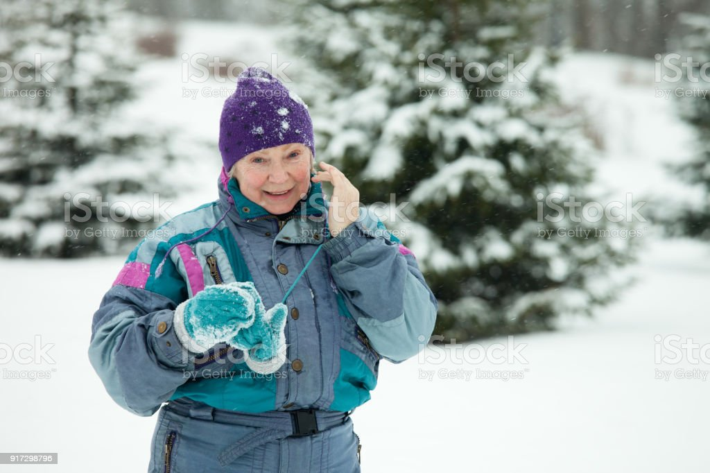 Senior woman on a sporty walk in the winter forest stock photo