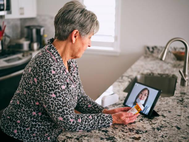 hogere vrouw op een virtueel bezoek van de arts - bezoek stockfoto's en -beelden