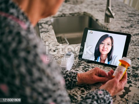 A senior aged woman in her home, talking to a doctor online in a virtual appointment.