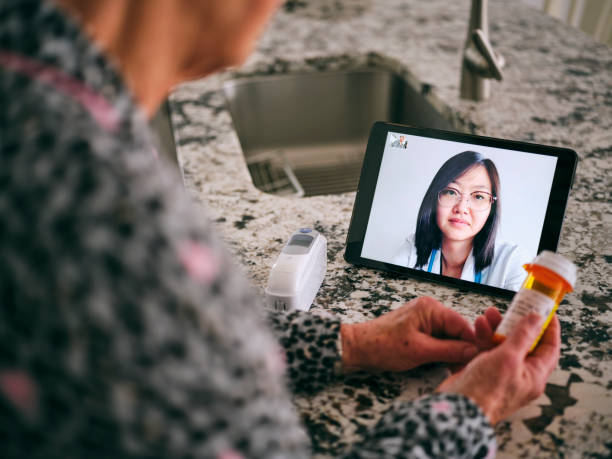Senior Woman on a Virtual Doctor Visit A senior aged woman in her home, talking to a doctor online in a virtual appointment. technology stock pictures, royalty-free photos & images