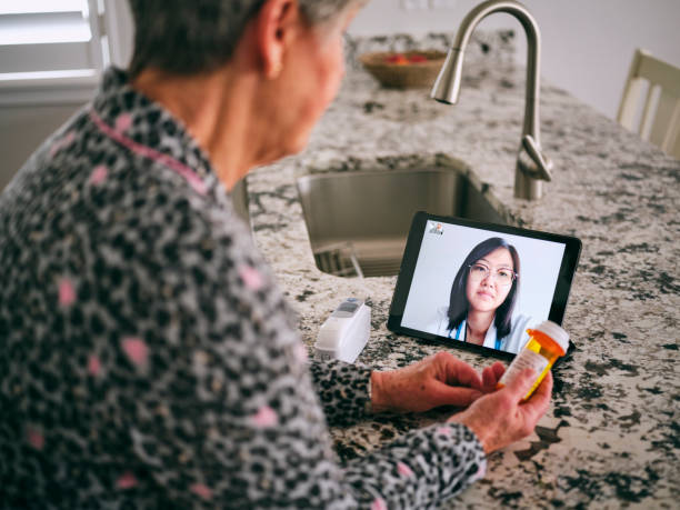 Senior Woman on a Virtual Doctor Visit A senior aged woman in her home, talking to a doctor online in a virtual appointment. flatten the curve stock pictures, royalty-free photos & images
