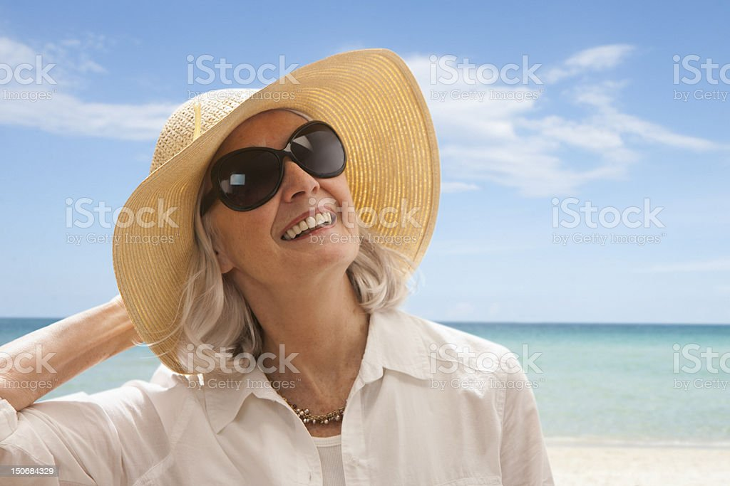 Senior woman on beach holding hat stock photo