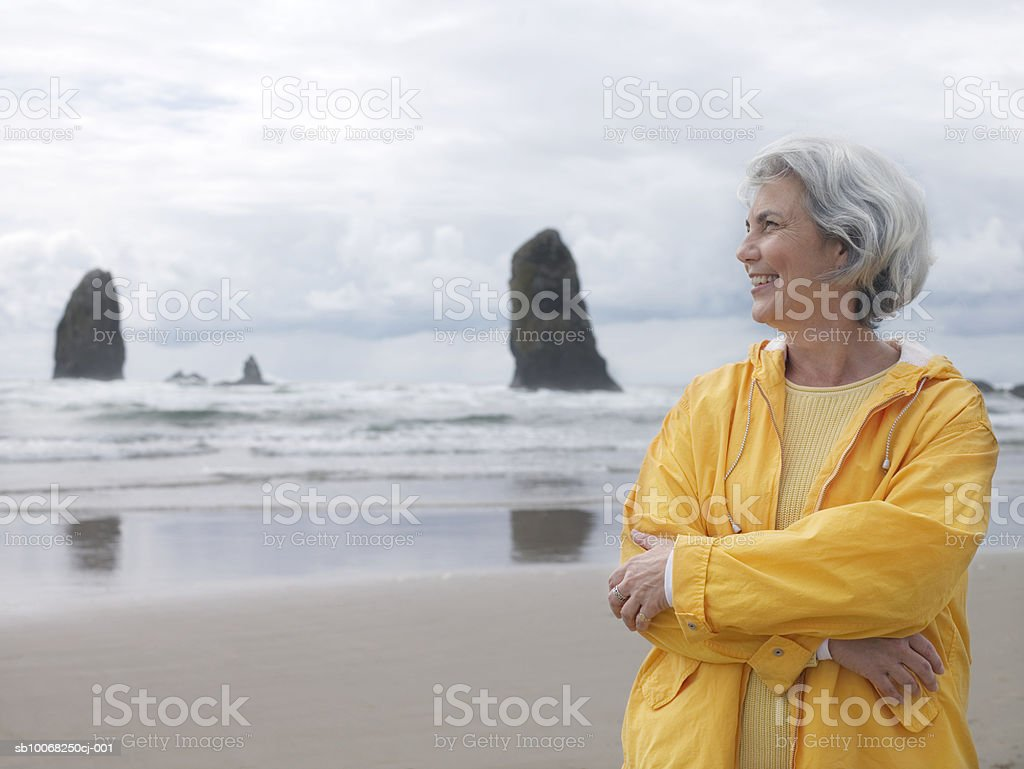 Senior woman on beach with arms crossed, smiling royalty free stockfoto