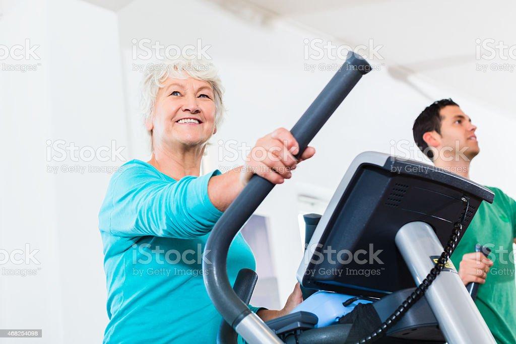Senior woman on elliptical trainer exercising in gym stock photo