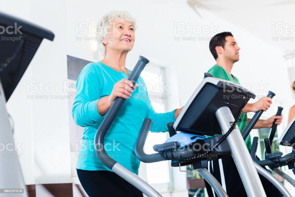 高級橢圓訓練儀,在健身房鍛煉身體的女人 免版稅 stock photo