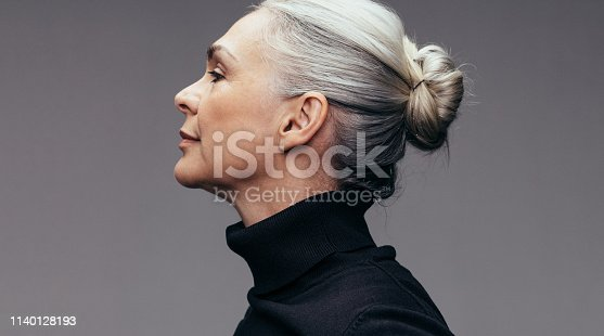 Side view of senior woman on gray background. Profile view of mature woman in black casuals.