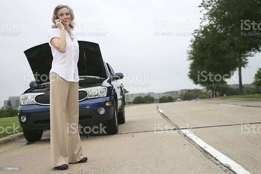 Senior Woman on her Cellphone by a Broken-down Car royalty-free stock photo